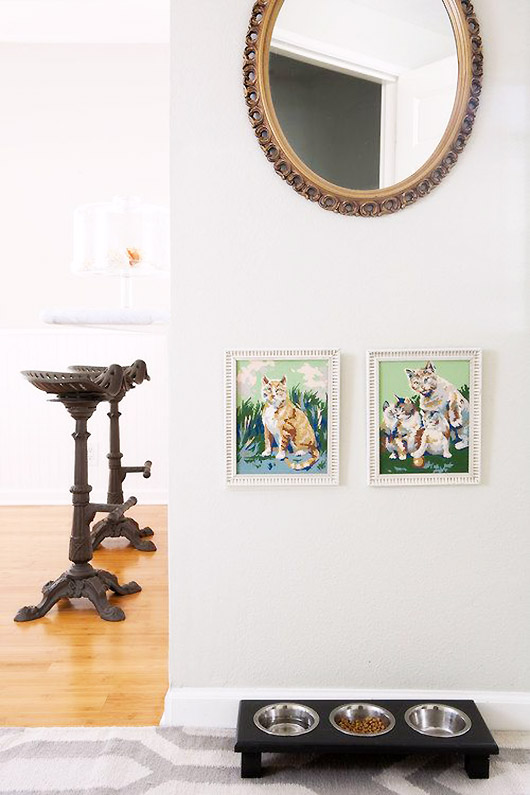 ornate oval mirror hung above two white framed cat paintings with a black raised cat feeder below / sfgirlbybay