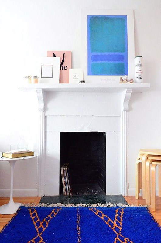 white walls in modern bohemian room with fireplace and bright blue moroccan rug and colorful art leaned on mantel above / sfgirlbybay