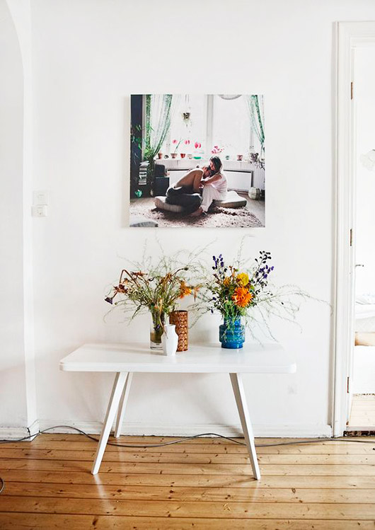 white walls with enlarged wall print and colorful vases with flowers on white table below / sfgirlbybay