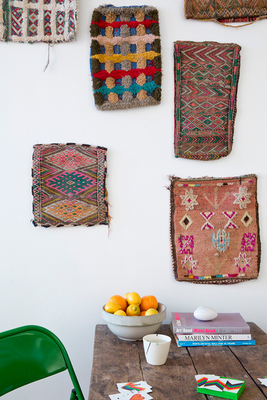 colorful woven wall tapestries hung above a rustic wood table and dark green chair / sfgirlbybay