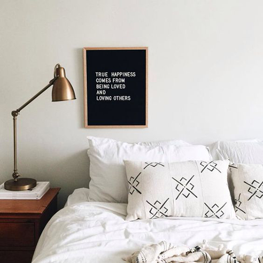 bedroom with wood nightstand, brass task lamp and back and white message board / sfgirlbybay
