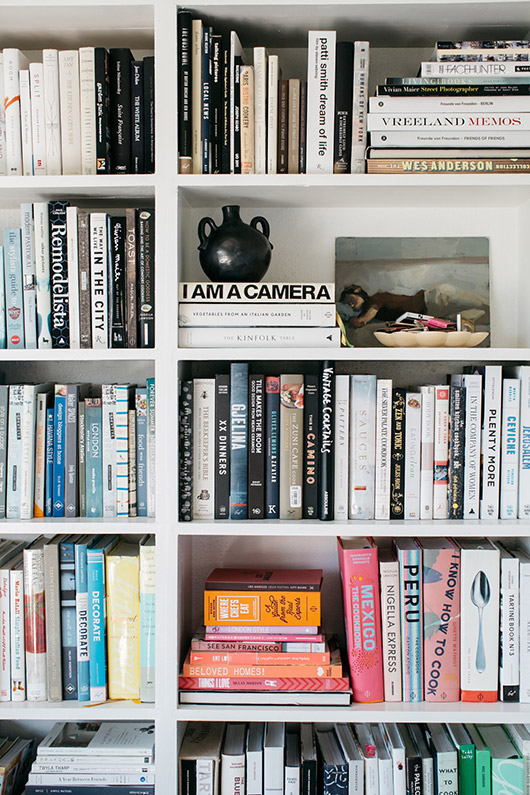 white built-in bookcase with color blocked books. / sfgirlbybay