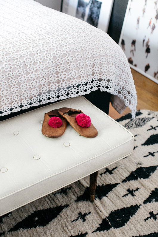 leather moroccan slippers with pom poms at foot of bed. / sfgirlbybay