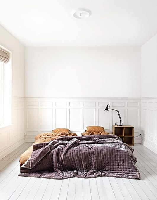 white bedroom with painted floors and tan sheets with purple velvet bedspread. / sfgirlbybay
