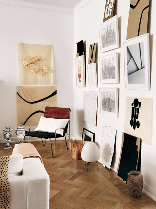 art on walls with un-framed prints leaning on top of frames. / sfgirlbybay
