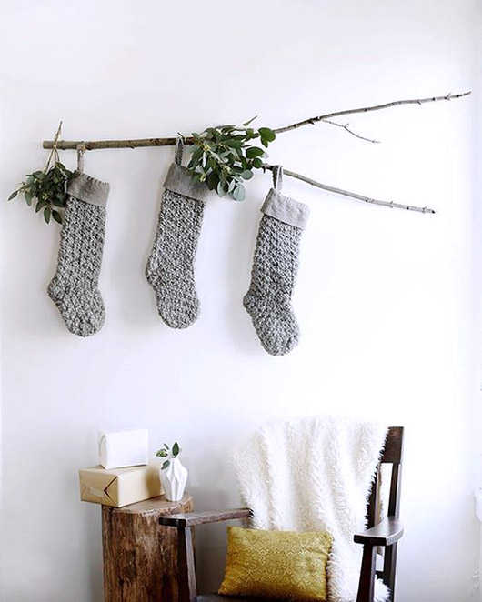 gray knit christmas stockings hung on a branch. / sfgirlbybay