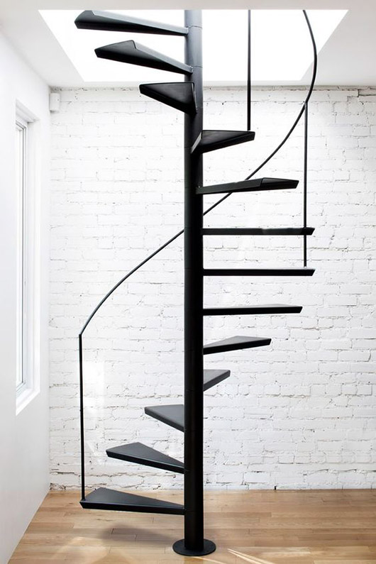 black spiral staircase with white brick wall and wood floors. / sfgirlbybay