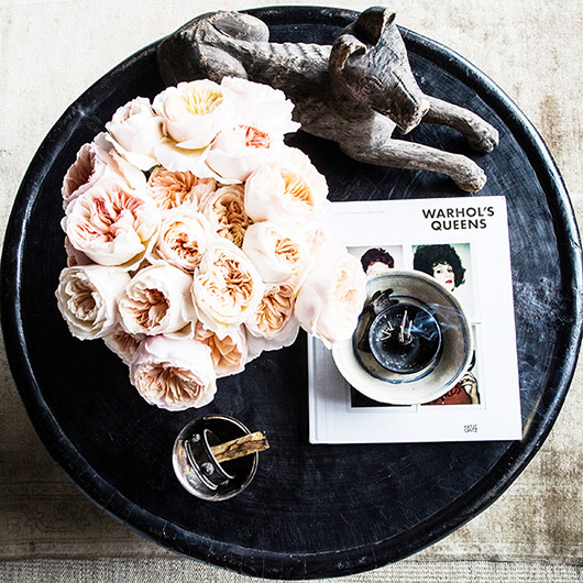 black coffee table styled with flowers and accessories. / sfgirlbybay