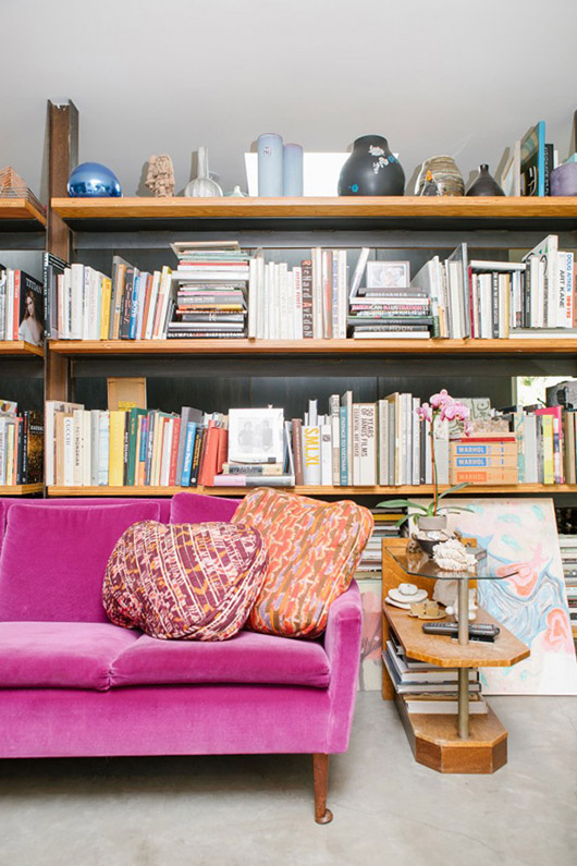 bookshelves behind bright pink sofa. / sfgirlbybay