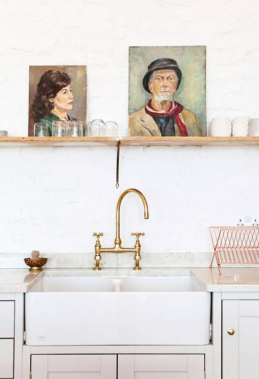 vintage portrait paintings in a white modern kitchen. / sfgirlbybay