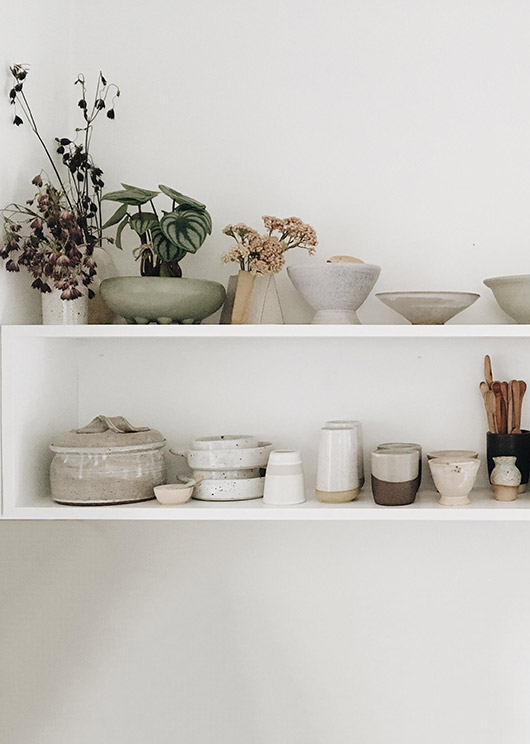 ceramics on open white shelves. / sfgirlbybay