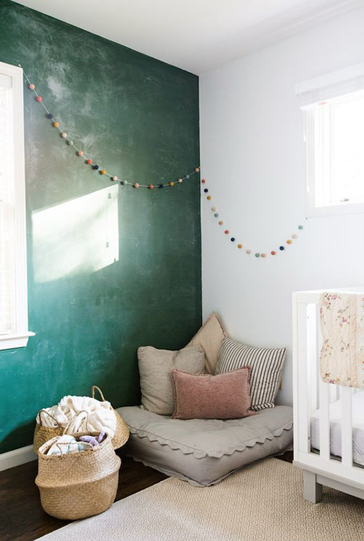 green wall with pom pom garland. / sfgirlbybay