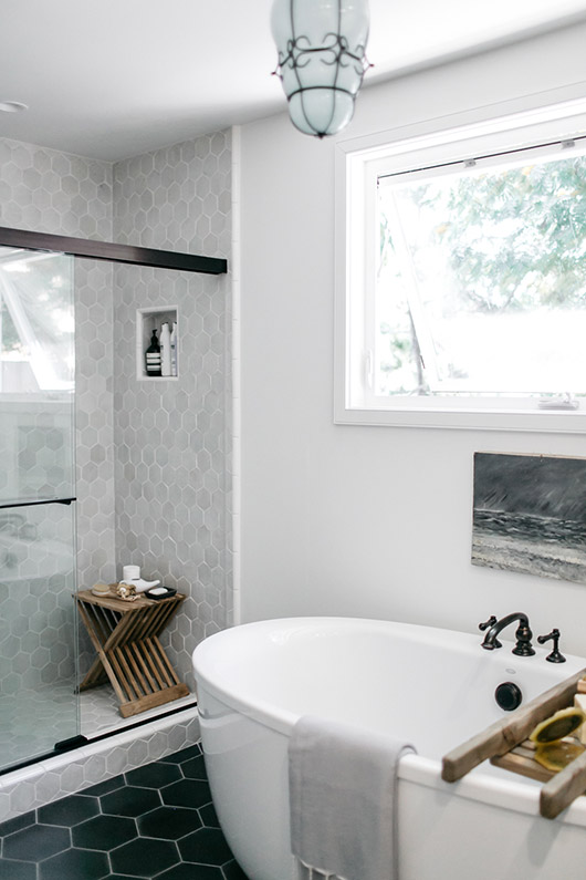 Clé tiles' zellige white weathered hex in shower with wood table. / sfgirlbybay