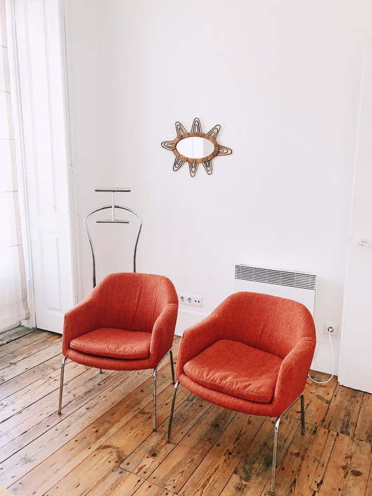 matching red chairs and wicker mirror. / sfgirlbybay