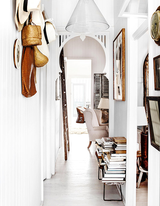white hallway with book collection on bench. / sfgirlbybay