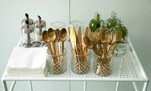 gold and green tablewares on white cart. / sfgirlbybay
