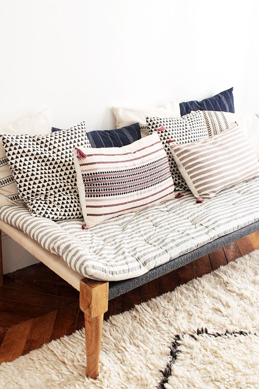 upholstered bench with throw pillows in eclectic french home. / sfgirlbybay
