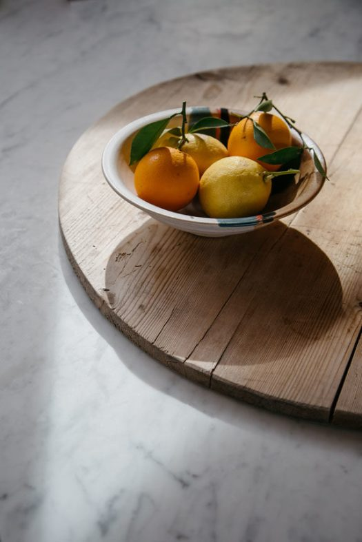 sunlight citrus fruit in bowl on wood cutting board. / sfgirlbybay