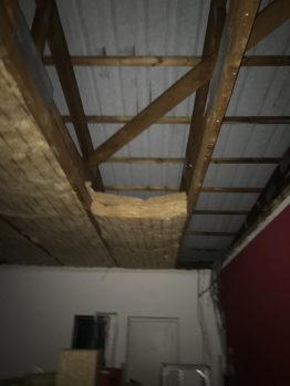 Die verrußte Dachdämmung ist raus - hier wird gerade die neue Dachdämmung eingebaut.