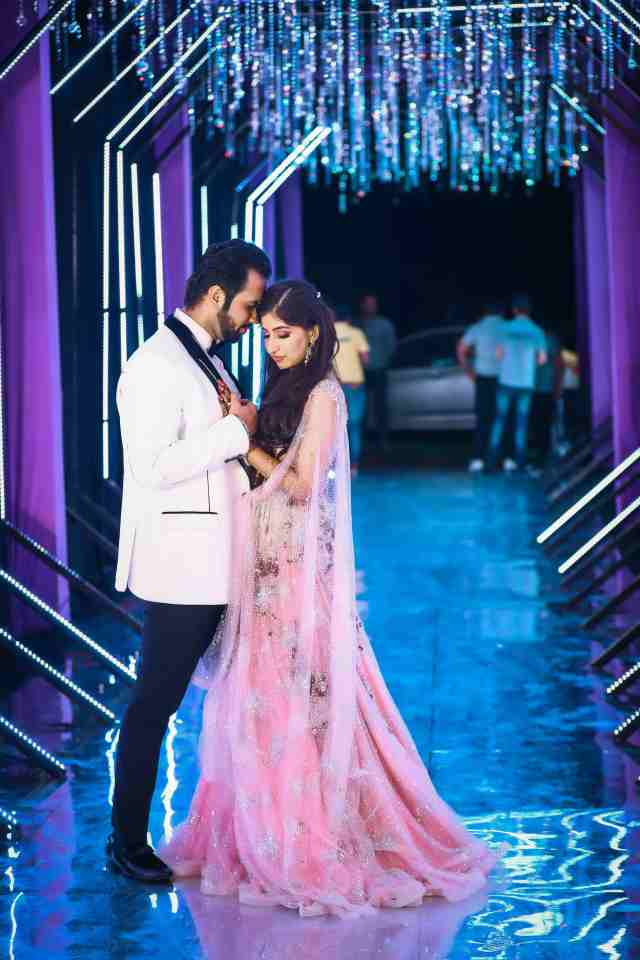 Ayushi in a pink lehenga by Dolly J and Aryan in a white tuxedo