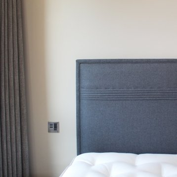 Bespoke upholstered headboard and blackout lined curtains