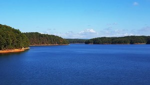Panarama of a dark blue lake with red clay banks and evergreen forests