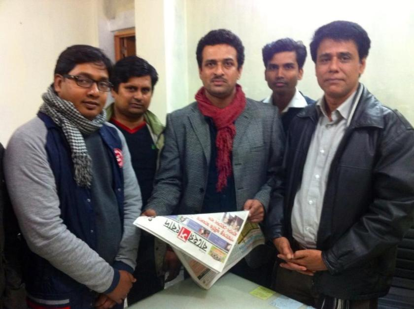 Azizur Rahim Peu (on right) and colleagues with a copy of the daily newspaper he edited Baher Shongbad