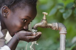 little girl drinking water from spicket