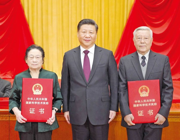 President Xi Jinping (center) with Zhao Zhongxian (right) and Tu Youyou after he presented them with China's top science award in Beijing yesterday for their outstanding contributions to scientific and technological innovation. Zhao is a leading scientist in the field of superconductivity, while Tu won the 2015 Nobel Prize in Physiology or Medicine for her work on malaria. — Xinhua