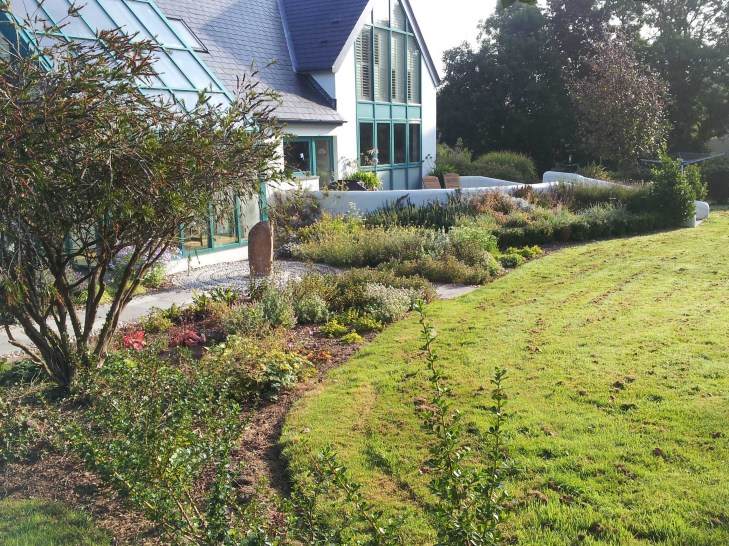 Newly planted beds with a standing stone set into a pebble mosaic created by Shani.