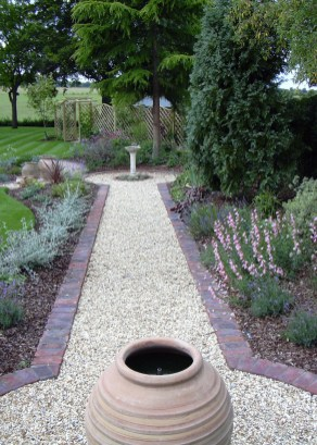 This simple path leads to a water feature past fragrant beds full of colour in this medium sized garden.