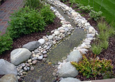 Garden design showing the use of water. Gentle water rill brings relaxing sounds and a place for birds and butterflies to catch a drink and even have a bath in this medium sized garden.