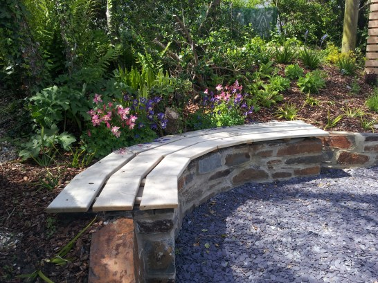 Natural planting behind this stone and oak bench in this coastal garden.