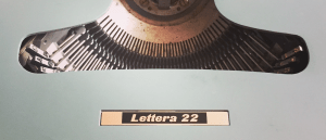 The top of a pale green Underwood-Olivetti Lettera 22 manual typewriter with typebars visible.