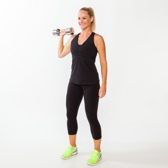 Stand with feet hip-width apart, knees slightly bent, and abs engaged, holding a dumbbell in right hand just above shoulder so palm faced front. Extend left arm down by side.