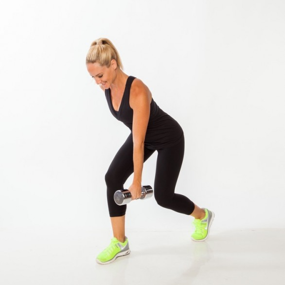 Stand in a split stance with right foot forward, holding a dumbbell with left hand. Bend both knees and, keeping abs tight and spine naturally straight, hinge forward from hips about 45 degrees, reaching left arm toward the floor and placing right hand on lower back to help ensure proper form.
