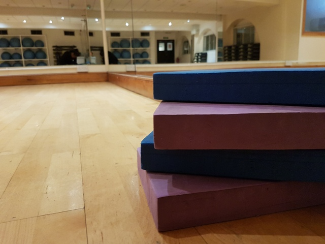 Pilates equipment staked on the floor in a fitness studio