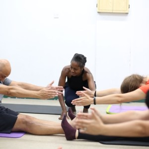 Men and women doing Pilates stretch on floor in Pilates class