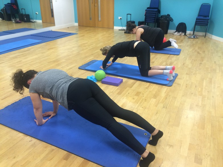 Three women in Pilates class doing different types of push up