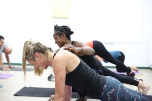 Pilates client smiles whilst being helped to do a pushup