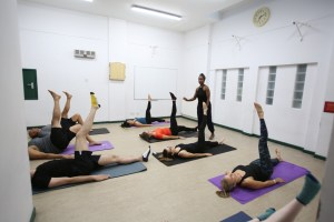 People lying on the floor in a Pilates class each with one leg raised