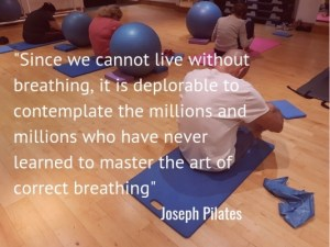 Pilates quote overlayed on photo of people sitting in a Pilates class breathing