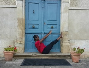 Woman in Pilates teaser in front of blue door