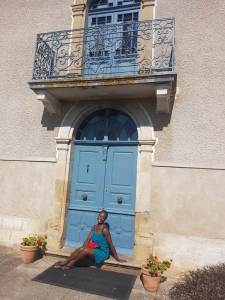Woman in green dress sitting on the doorstep infront of a blue door, under a balcony