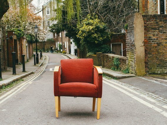 A red armchair sitting in the middle of a road