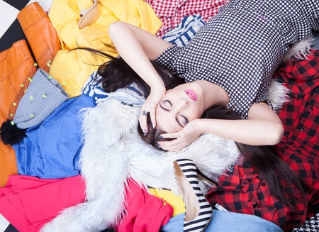 39092416 - nothing to wear concept, woman lying on a pile of clothes