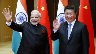Indian Prime Minister Narendra Modi (L) and Chinese President Xi Jinping wave to journalists. (Photo courtesy of Quartz)