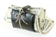 Leather wallet with some dollars inside on white background