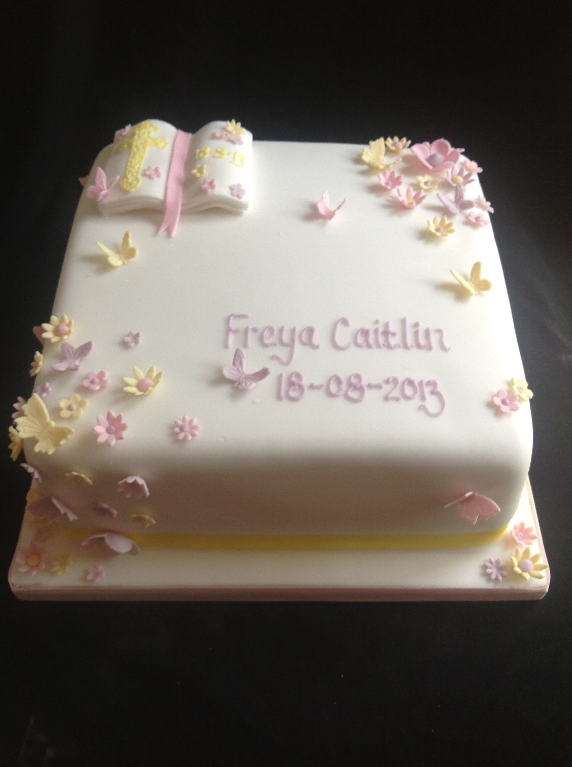 A square cake with a little bible in the top left corner, little pastel coloured butterflies and blossom flowers