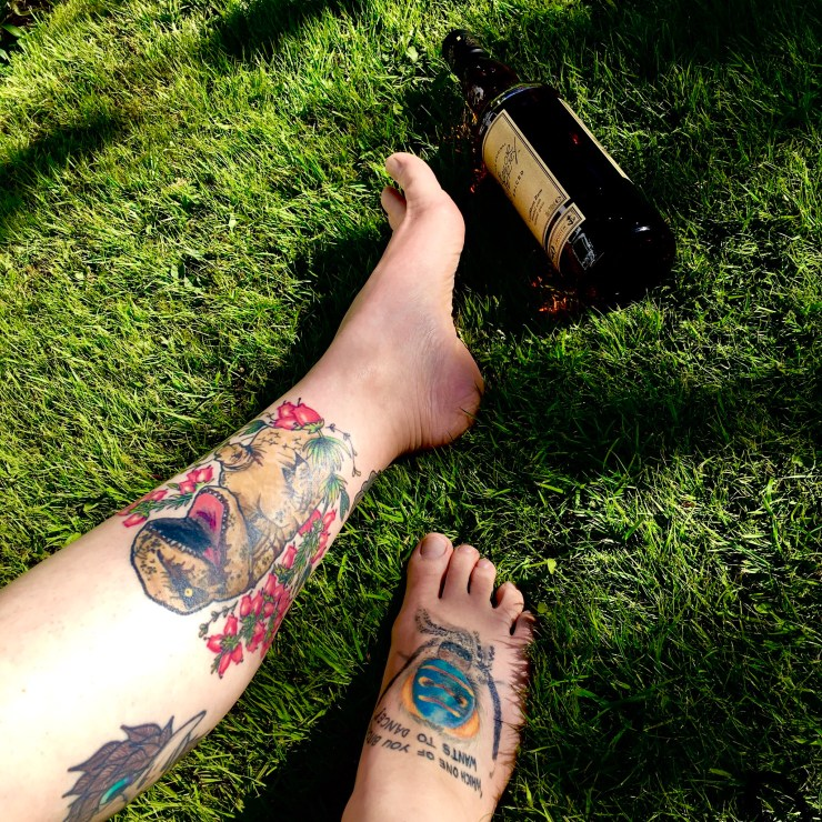 Picture of tattooed legs and bottle of alcohol